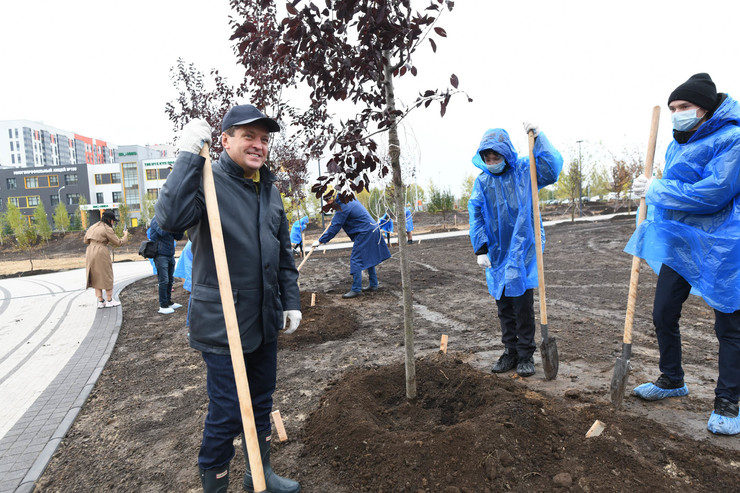 Ilsur Metshin together with schoolchildren plants cherry trees in the new park in Salavat Kupere